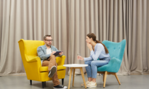 Two people sat on comfy chairs around a low table having a meeting
